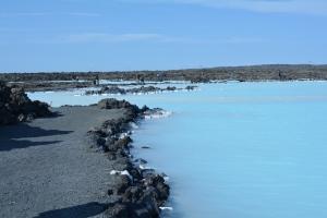 O contraste do azul claro da água com o solo vulcânico é impressionante