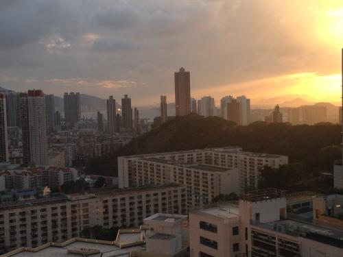 Por do sol entre montanhas e mar (o mar está entre os prédios, no centro da foto)
