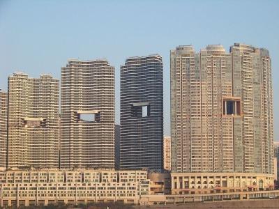é comum ver estes prédios com buracos no meio, em Hong Kong. Foto: shottapaul/Flickr